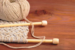 Piece of knitted cloth with threads and wooden needles on wooden table Stock Photography