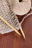 Piece of knitted cloth with threads and wooden needles on wooden table Royalty Free Stock Photography