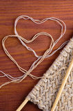 Piece of knitted cloth with wooden needles and thread hearts on wooden table Royalty Free Stock Images