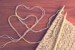 Piece of knitted cloth with wooden needles and thread hearts on wooden table vintage filtered Stock Photo