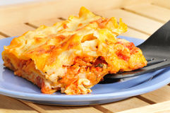Piece of lasagna on a blue plate on a wooden salver. Royalty Free Stock Images