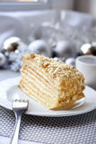 Piece of layer cake with custard and walnuts. On a plate with Christmas balls on the background Stock Photography