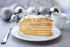 Piece of layer cake with custard and walnuts. On a plate with Christmas balls on the background Stock Photo
