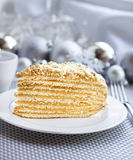 Piece of layer cake with custard and walnuts on a plate. With Christmas balls on the background Royalty Free Stock Photography