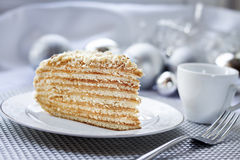 Piece of layer cake on a plate with Christmas balls on the backg Stock Photos