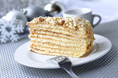 Piece of layer cake on a plate with Christmas balls on the backg Royalty Free Stock Photography