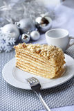 Piece of layer cake on a plate with Christmas balls on the backg Stock Image