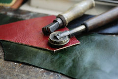 Piece of leather and some tools. To work it Royalty Free Stock Image