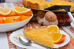 Piece of Lemon and almond pie on plate with oranges Royalty Free Stock Images