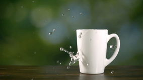 Piece of lemon drop in cup of hot water, super slow motion hd video stock footage