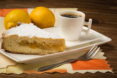 A piece of lemon pie and a cup of tea on the wooden background. A piece of lemon cake and a cup of tea on the wooden background Stock Photo