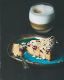 Piece of lemon, ricotta, almond, raspberry cake and latte Stock Image