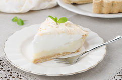 Piece of lemon tart with meringue decorated with fresh mint on a Royalty Free Stock Photos
