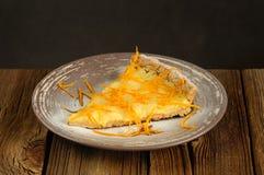 Piece on lemon tart with orange peel. On wooden background Royalty Free Stock Photo