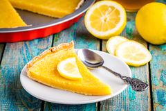 Piece of lemon tart on a plate. With lemons on rustic blue table Stock Photography