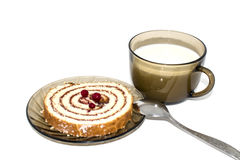 A piece of the loaf and Cup of milk. A piece of sponge cake roll and a Cup of milk for Breakfast Royalty Free Stock Photography