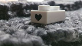 Piece of love. Little white plastic brick of constructor with symbol oh heart painted on it lying on knitted gray scarve Stock Photo