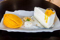 A piece of mango cheese cake on table wooden Stock Photo