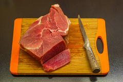 Piece of meat and knife on cutting board. On black background Stock Image