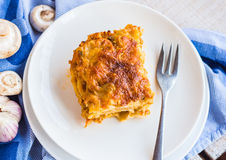Piece of meat lasagna with mushrooms, cutlery, Italian food Royalty Free Stock Image