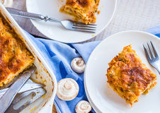 Piece of meat lasagna with mushrooms, cutlery, Italian food Royalty Free Stock Images