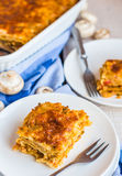 Piece of meat lasagna with mushrooms, cutlery, Italian food Stock Images