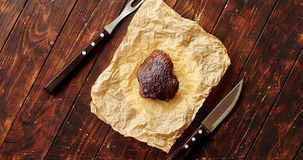 Piece of meat on napkin. From above view of fried piece of meat laid on paper napkin with knife and fork placed near on wooden background stock footage