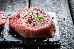 Piece of meat with rosemary and pepper on black rock Royalty Free Stock Photo