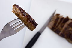 Piece of medium rare steak. On a fork royalty free stock images