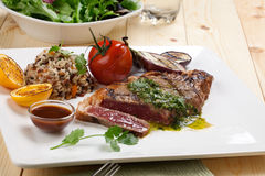 Piece of Medium Rare Steak with Spicy Herb Sauce. Close of of one piece cut of medium rare grilled steak with spicy herb sauce, garnished with grilled vegetables royalty free stock photography