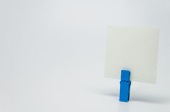Piece of Memo paper clamped by blue wooden clip with white background and selective focus Royalty Free Stock Photo