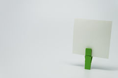 Piece of Memo paper clamped by green wooden clip with white background and selective focus Stock Photography