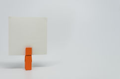 Piece of Memo paper clamped by orange wooden clip with white background and selective focus Stock Photo