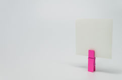 Piece of Memo paper clamped by pink wooden clip with white background and selective focus Royalty Free Stock Photography