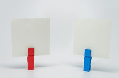 Piece of Memo paper clamped by red and blue wooden clip with white background and selective focus Stock Image