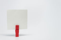 Piece of Memo paper clamped by red wooden clip with white background and selective focus Stock Photo
