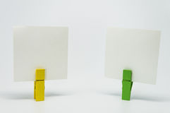 Piece of Memo paper clamped by yellow and green wooden clip with white background and selective focus Royalty Free Stock Photo
