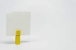 Piece of Memo paper clamped by yellow wooden clip with white bacckground and selective focus Royalty Free Stock Photography