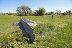 A piece of metal debris wrapped around a fence post by a tornado. Stock Photo