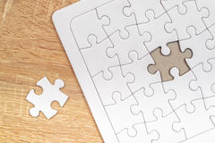 Piece missing from jigsaw puzzle on wooden table Royalty Free Stock Image