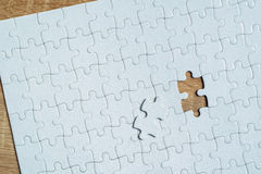 Piece missing from jigsaw puzzle on wooden table Stock Image