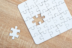 Piece missing from jigsaw puzzle on wooden table Royalty Free Stock Photo