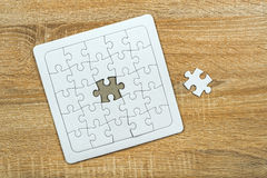 Piece missing from jigsaw puzzle on wooden table Royalty Free Stock Images