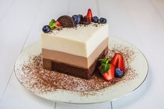 A piece of a mousse cake three chocolate stands on a plate, sprinkled with grated chocolate, and decorated with berries. And biscuits. A plate with a cake stock image