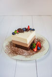 A piece of a mousse cake three chocolate stands on a plate, sprinkled with grated chocolate, and decorated with berries stock photo