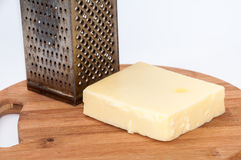Piece of mozzarella cheese and metal grater on a kitchen wooden Royalty Free Stock Photos