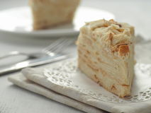 Piece of multi layered cake close-up. Mille feuille dessert. Crumbs decorated torte on white doily upon wooden table. Food background, blur. Selective focus on Royalty Free Stock Images