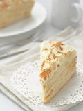 Piece of multi layered cake close-up. Mille feuille dessert. Crumbs decorated torte on white doily upon wooden table. Food background, blur. Selective focus on Royalty Free Stock Photos