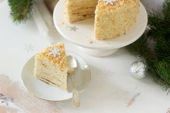 A piece of Napoleon cake in Christmas or New Year decoration on a light background. Rustic style. Stock Photos