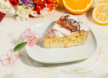A piece of neapolitan easter pie sprinkled with icing sugar and decorated with almond blossom,freesia and fresh fruits. Royalty Free Stock Photo